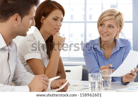 Business team in discussion of work document, working together in office. - stock photo