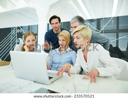 Business team in office looking at laptop computer monitor - stock photo
