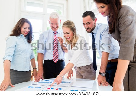 Business team in strategy meeting discussing numbers and data - stock photo