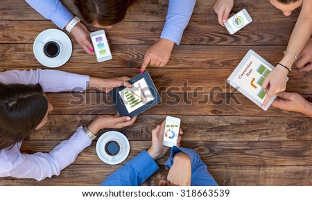 Business Team Interaction  Top View of Arms of Group Young Business People Discussing Data on Electronic Gadgets Related to Social Media Marketing Impact - stock photo