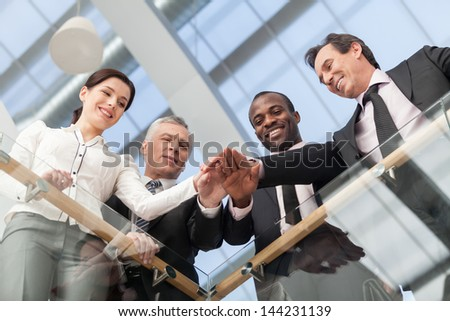 Business team joining their hands at office. Bottom View - stock photo