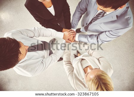 Business team keeping their hands in pile - stock photo