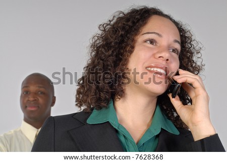Business team leader on the phone with her support staff behind her; isolated on gray - stock photo