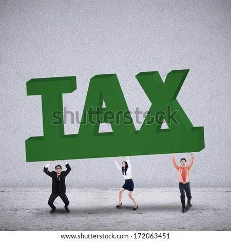 Business team lifting a big word of TAX on grey background - stock photo