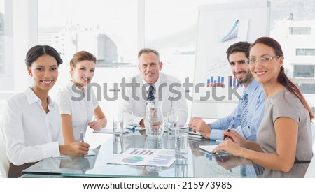 Business team looking at camera in the meeting room - stock photo