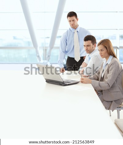Business team looking at laptop computer screen at bright office. Sitting at table, serious, wearing suit. Copyspace.
