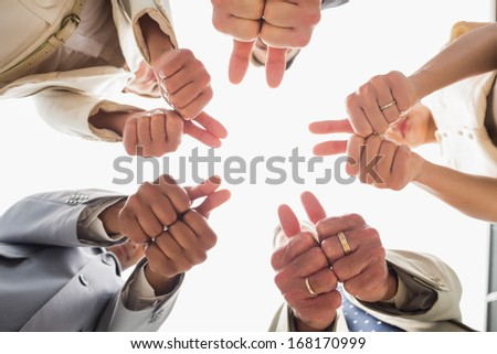 Business team looking down at the camera showing thumbs up in the office