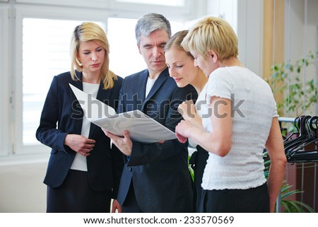 Business team looking together at contract in office meeting - stock photo