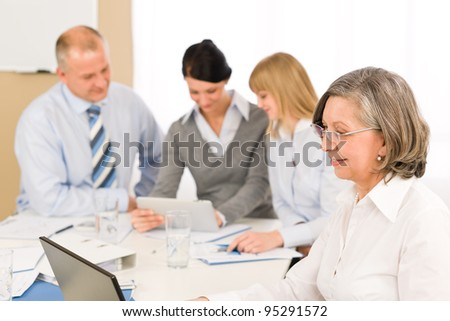 Business team meeting executive senior businesswoman with colleagues looking tablet - stock photo