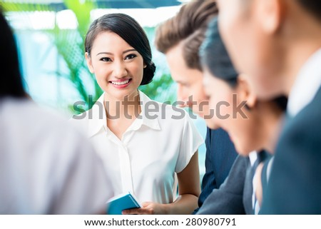 Business team meeting of Asian and Caucasian executives, Chinese woman is looking into the camera - stock photo