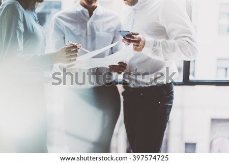 Business team meeting,work process.Photo professional crew working with new startup project.Project managers near window.Analyze business plans, smartphone hands. Blurred, film effect.Horizontal - stock photo