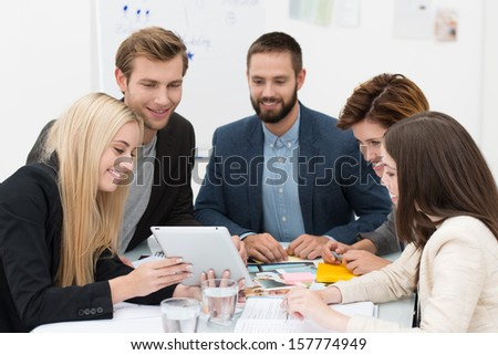 Business team of dedicated diverse young professionals sitting around a table with a tablet computer brainstorming - stock photo