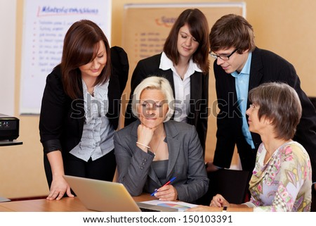 Business team of diverse young people gathered around a laptop looking at the screen with serious expressions - stock photo