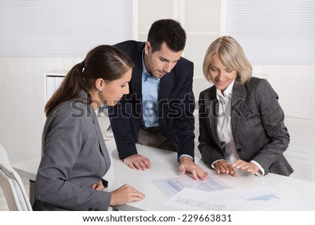 Business team of man and woman sitting around a table talking together in a meeting. - stock photo