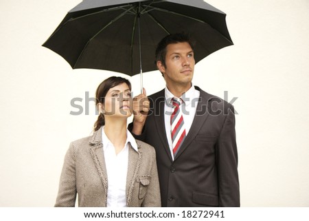 Business team of man and woman with umbrella - stock photo