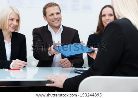 Business team of smiling professionals conducting a job interview reaching to take the file of credentials from the female applicant - stock photo
