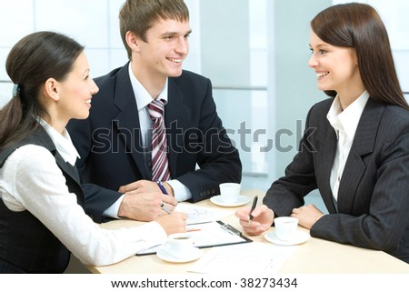 Business-team of three smiling people discussing new working ideas