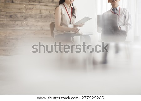 Business team of two in an office looking at some data on a laptop - stock photo