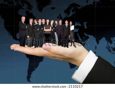 business team on a hand with the earth map in the background - stock photo