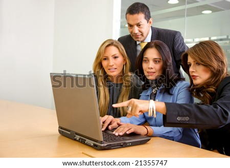 business team on a laptop in an office smiling