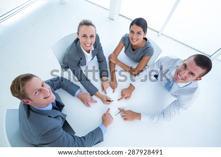 Business team pointing clipboard in the office - stock photo