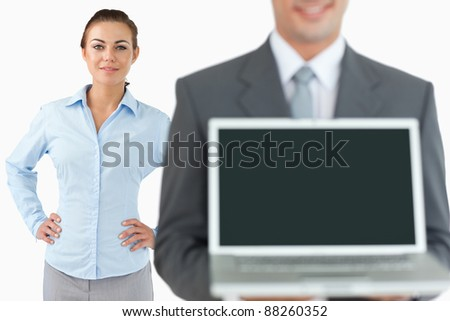 Business team presenting laptop against a white background
