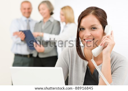 Business team pretty businesswoman calling phone happy colleagues looking folder