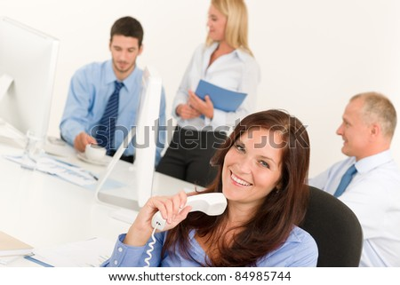 Business team pretty businesswoman holding phone happy colleagues around table - stock photo
