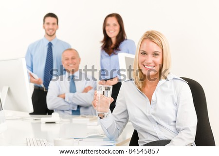 Business team pretty young businesswoman portrait with colleagues around table