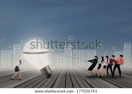 Business team pulling a big light bulb with a woman pushing - stock photo