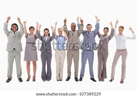 Business team raising their arms with the thumbs up against white background - stock photo