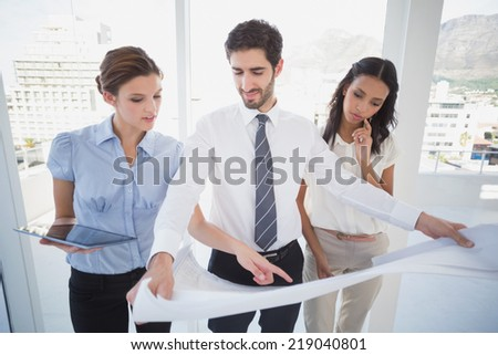 Business team reading a plan in an office - stock photo