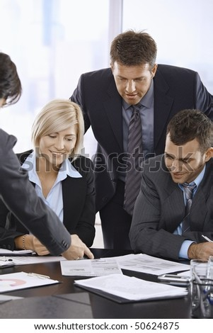 Business team reviewing documents in office smiling. - stock photo