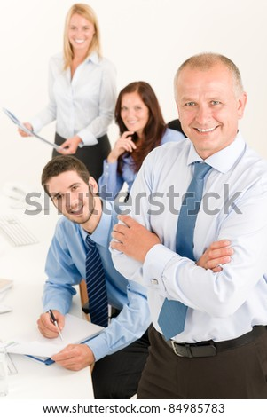 Business team senior businessman with attractive happy colleagues in office - stock photo