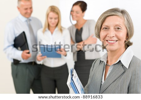 Business team senior businesswoman in front with attractive happy colleagues