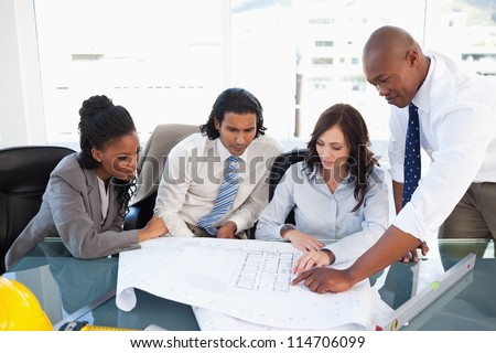 Business team seriously working with flipchart sheets - stock photo
