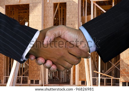 Business team shaking hands while closing a deal - stock photo