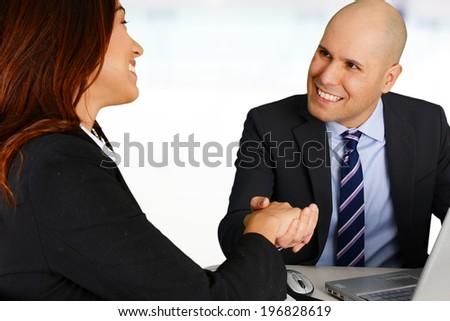 Business team shaking hands while in their office - stock photo