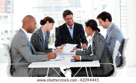 Business team showing ethnic diversity in a meeting smiling at the camera - stock photo