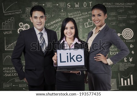 Business team showing like on laptop over chalkboard background - stock photo