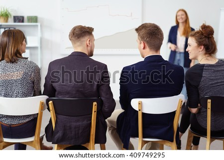 Business team sitting in a line discussing a presentation with their team leader standing in front listening to them
