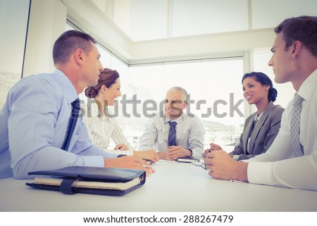 Business team sitting together around the table in the office - stock photo
