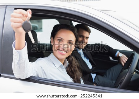 Business team smiling and driving in the car - stock photo