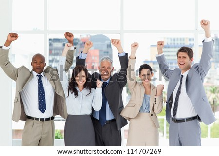 Business team smiling and standing upright with arms raised in success - stock photo