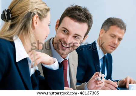 Business team smiling and talking together during a working meeting in office - stock photo