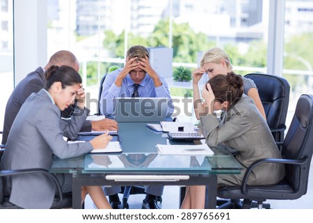 Business team smiling at camera in the office - stock photo