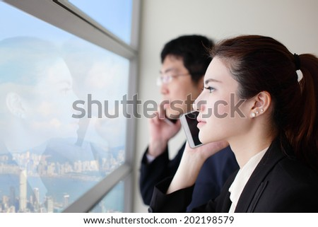 Business team speaking phone and looking through window with city background, asia, hong kong, asian - stock photo
