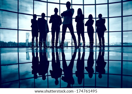 Business team standing against window with leader in front - stock photo