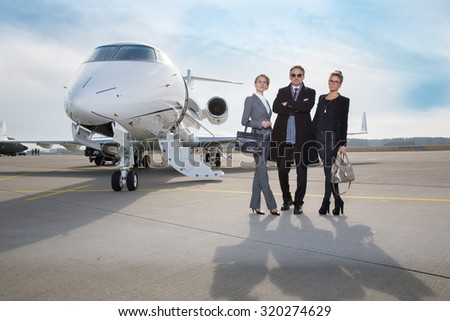 business team standing in front of private jet - stock photo