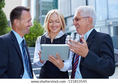 Business team talking and working with tablet computer outside - stock photo